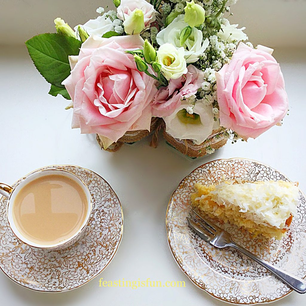 Afternoon tea set up with tea, cake and flowers.