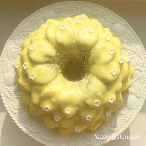 Lemon blueberry Bundt cake covered in a lemon glaze and decorated with small, white sugar flowers.