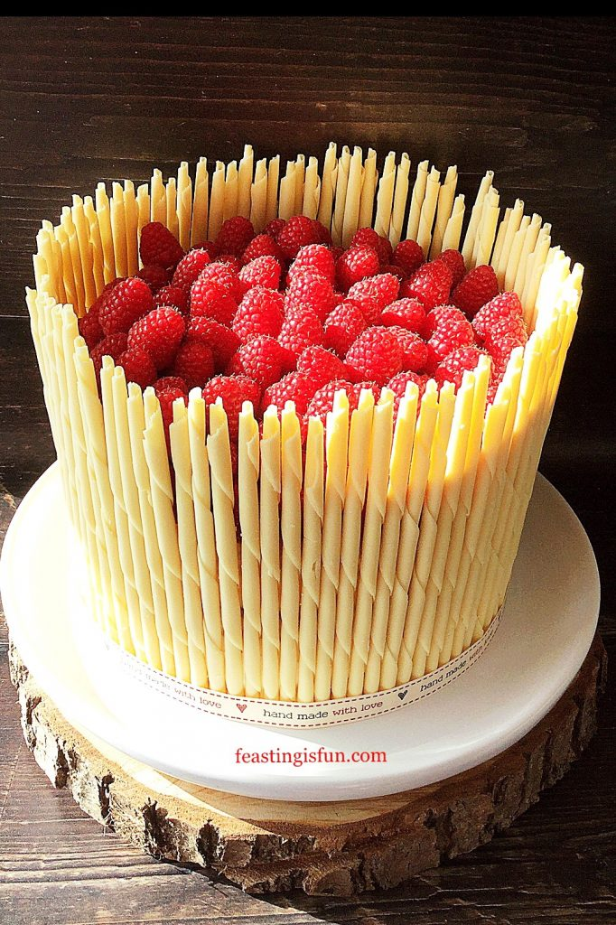 A white chocolate pencil surrounded, fresh fruit filled three sponge dessert.