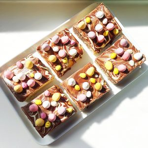 An Easter marbled traybake bake decorated with Cadbury's mini eggs.