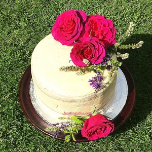 Three layer sponge filled with fresh jam and whipped vanilla buttercream and decorated with fresh roses. The dessert is set on a stand in a garden for garden parties and celebrating.