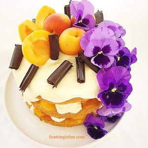 Three layer sponge filled with white chocolate ganache and apricots. Topped with fresh apricots, dark chocolate curls and vivid purple fresh pansies