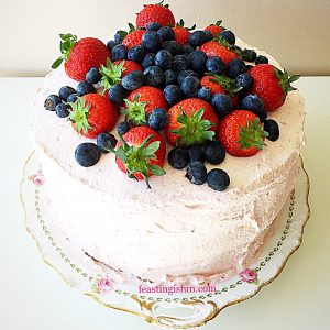 Summer mixed berry sponge covered with fresh fruit whipped cream and topped with an assortment of fresh fruit.
