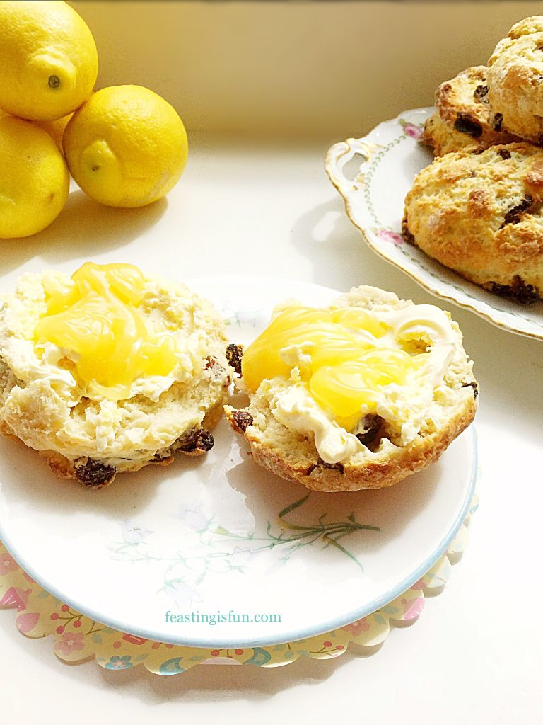 Cut scones topped with clotted cream and lemon curd on a pretty plate.