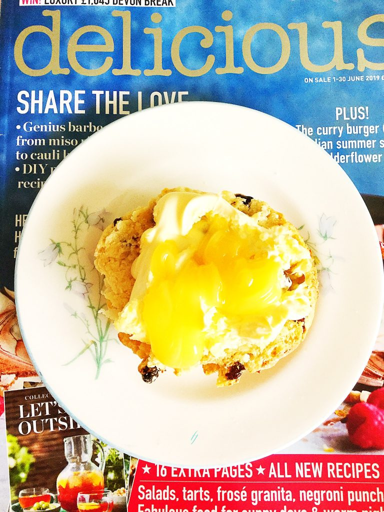 Delicious magazine with a plate on top containing a tasty afternoon sweet treat.