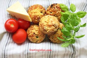 Savoury cheese scones in a lined basket with fresh tomatoes and basil and a wedge of cheddar cheese.