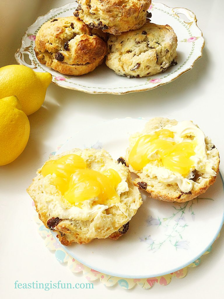 Split scones topped with clotted cream and lemon curd on a pretty plate. Fresh whole scones and lemons are in the background.