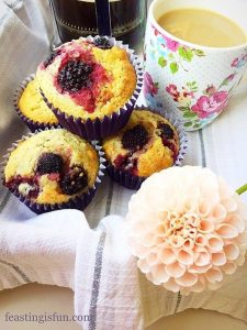 A lined breakfast tray with muffins, cafetière and mug of coffee and a blush coloured dahlia flower.