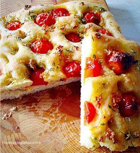 Tomato thyme garlic focaccia bread cut in half.