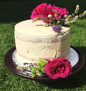 Raspberry Vanilla Celebration Cake semi covered in vanilla buttercream and decorated with fresh roses.