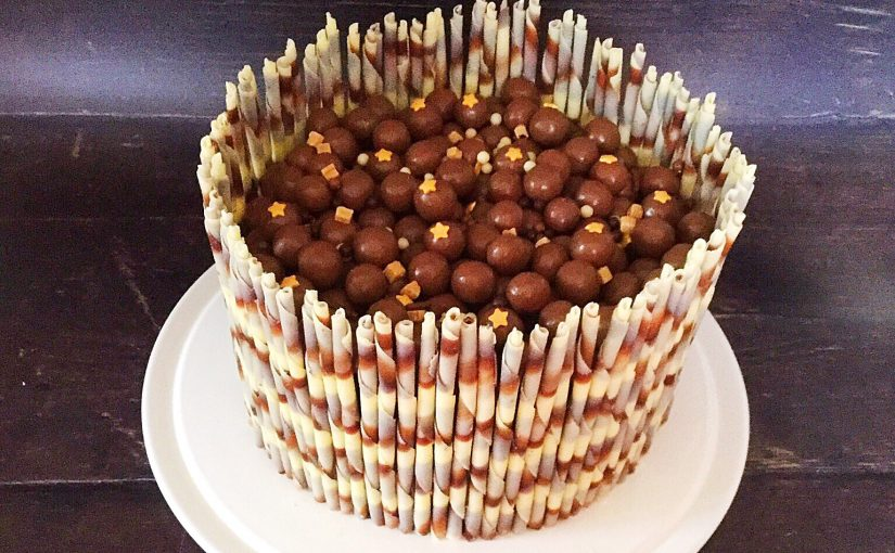 Chocolate marble celebration cake on a cream plate topped with Maltesers and sprinkles and surrounded with chocolate marble flutes.