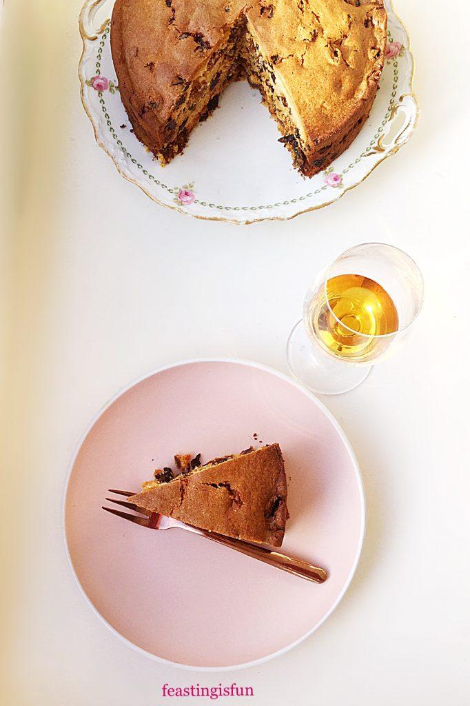 Overhead image of sliced cake served with a glass of amaretto liqueur.