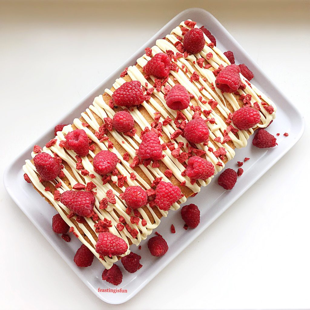Overhead image of a fresh berry sponge, decorated with raspberries.